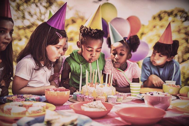 Nette Kinder, die zusammen auf der Kerze während einer Geburtstagsfeier durchbrennen stockfotos