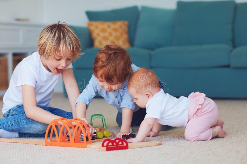 Nette Kinder, Geschwister, die zusammen Spielwaren auf dem Teppich zu Hause spielen stockfotografie