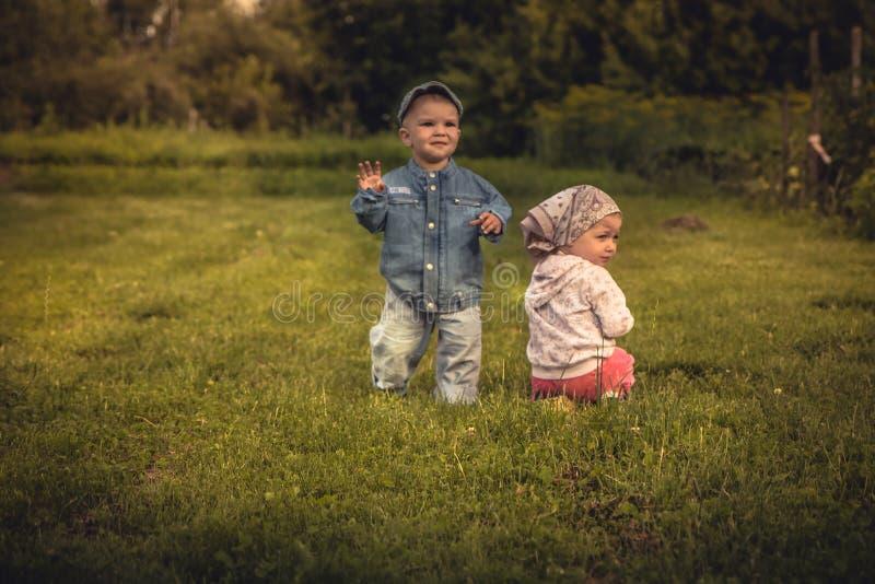 Nette Kinder Junge und Mädchen, die zusammen auf Gras bei Sonnenuntergang auf dem ländlichen Gebiet in der Landschaftssymbolisier stockbild