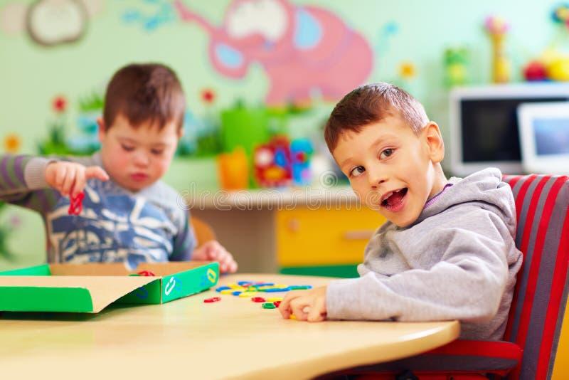 Nette Kinder mit dem speziellen Bedarf, der mit sich Entwickeln spielt, spielt beim Sitzen am Schreibtisch in Kindertagesstätte lizenzfreie stockbilder