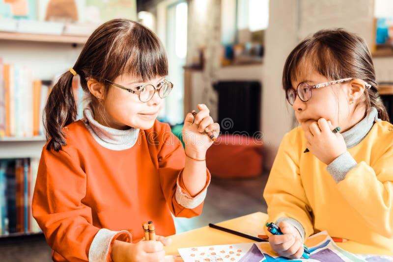 Nette Kinder mit Down-Syndrom miteinander sprechend und besprechend lizenzfreie stockfotos