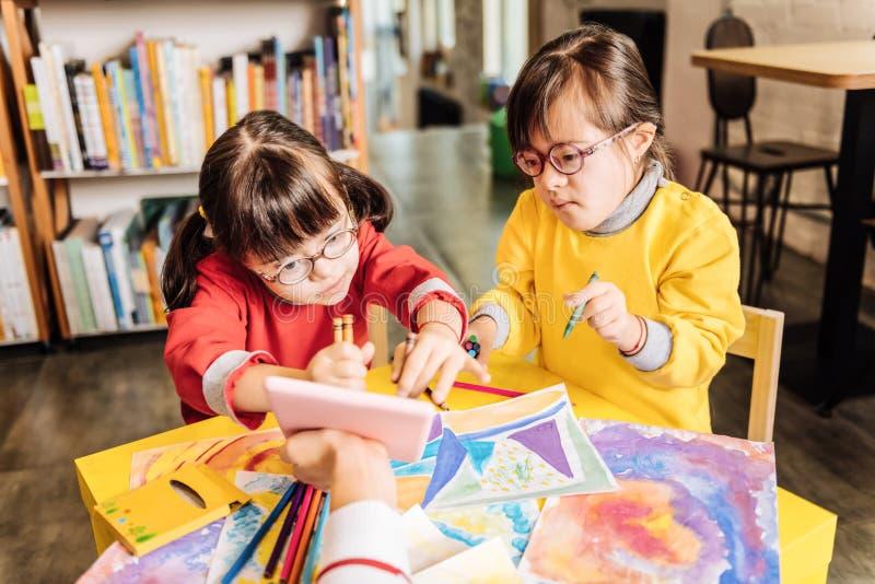 Nette Kinder mit Down-Syndrom studierend im einschließlichen Kindergarten lizenzfreies stockbild