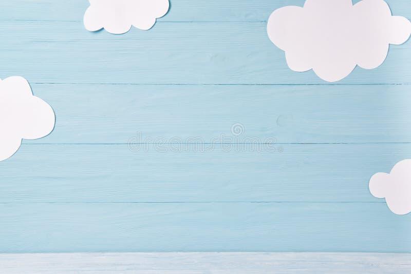 Nette Kinder oder Babyhintergrund, weiße Wolken auf dem blauen hölzernen Hintergrund stockfotografie