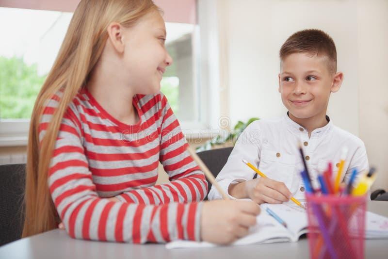 Nette kleine Grundschüler, die zusammen in Klasse zeichnen stockfoto