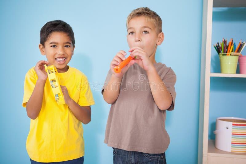 Nette kleine Jungen, die Musikinstrumente im Klassenzimmer spielen lizenzfreies stockfoto