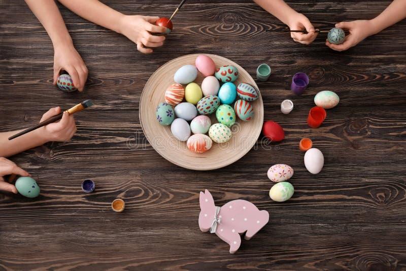Nette kleine Kinder, die bei Tisch Eier für Ostern malen lizenzfreie stockbilder