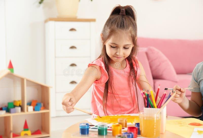 Nette kleine Kinder, die bei Tisch malen lizenzfreie stockbilder