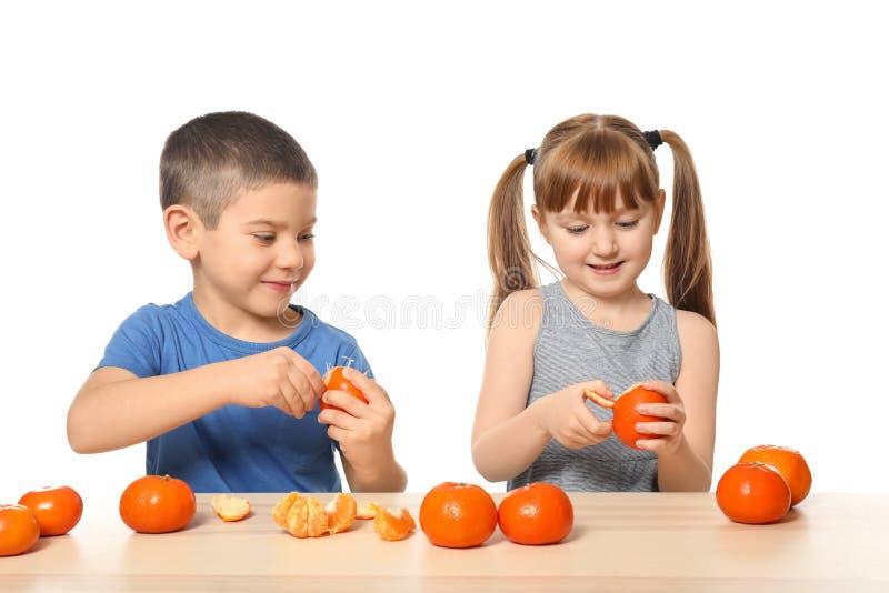 Nette kleine Kinder, die bei Tisch Zitrusfrucht auf weißem Hintergrund essen stockfotos
