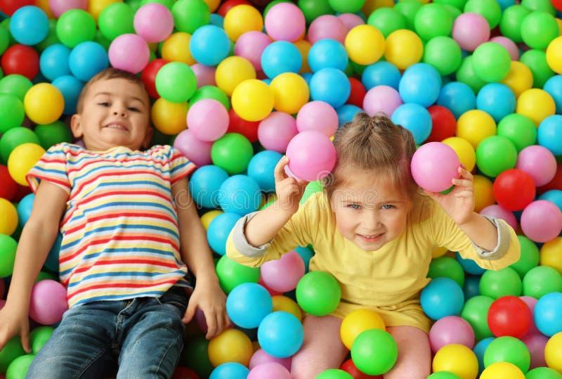 Nette kleine Kinder, die in der Ballgrube am Vergnügungspark spielen stockfotografie