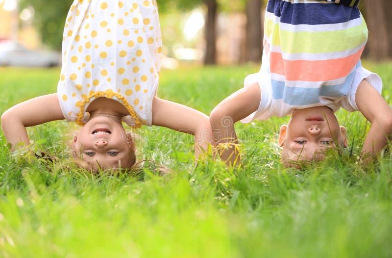 Nette kleine Kinder, die draußen auf Kopf stehen und Spaß haben stockfotografie