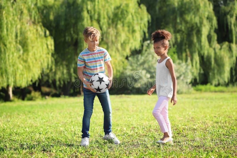 Nette kleine Kinder, die drau?en mit Ball spielen stockbild