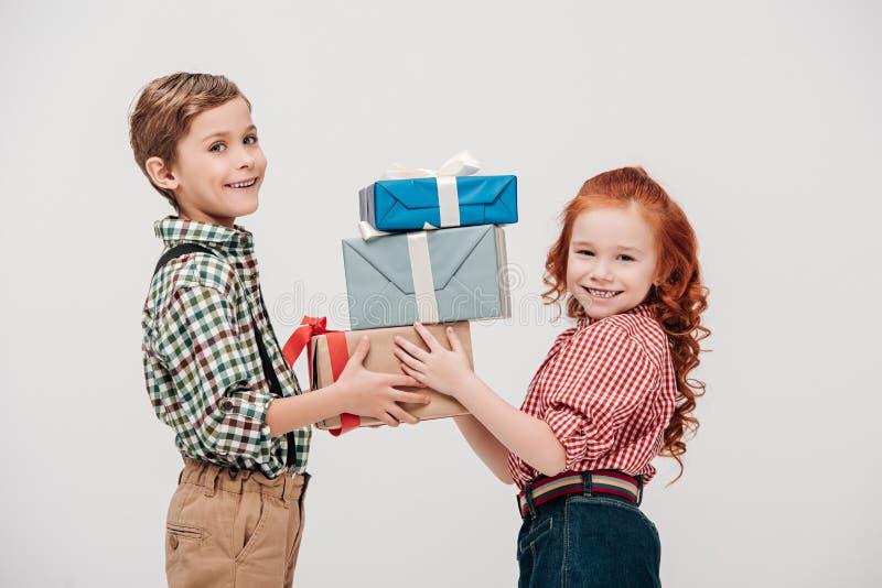 nette kleine Kinder, die Geschenkboxen halten und an der Kamera lächeln lizenzfreie stockfotografie