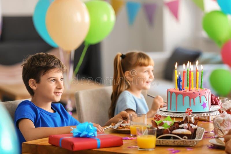 Nette kleine Kinder, die geschmackvolle Pizza und Bonbons an der Geburtstagsfeier essen stockbilder