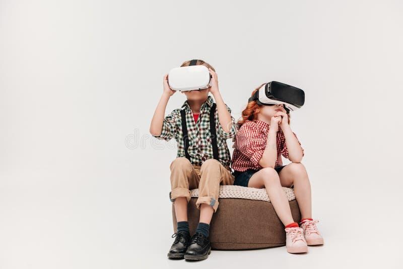 nette kleine Kinder, die Kopfhörer der virtuellen Realität sitzen und verwenden stockbild