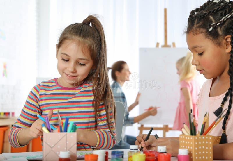 Nette kleine Kinder, die an malender Lektion zeichnen stockfotos