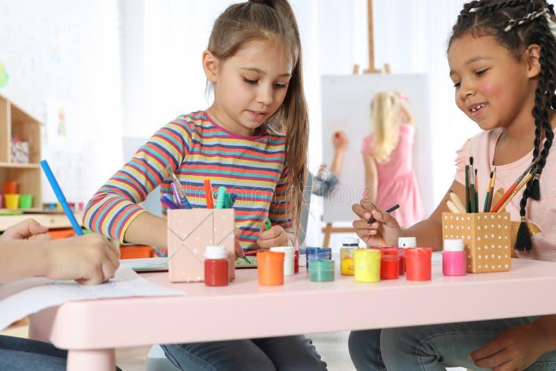 Nette kleine Kinder, die an malender Lektion zeichnen lizenzfreie stockfotos