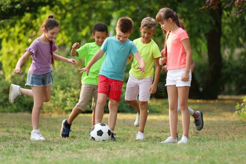 Nette kleine Kinder, die mit Fußball spielen lizenzfreie stockbilder