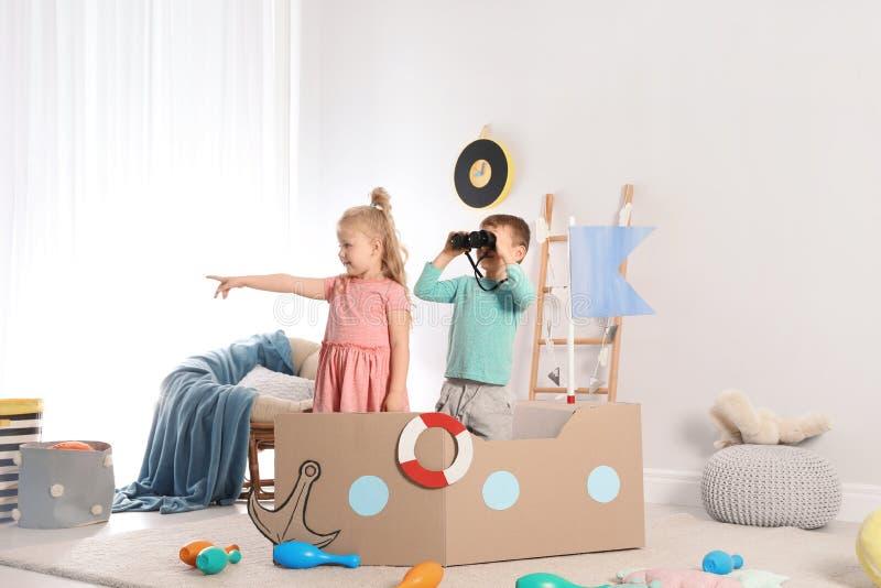 Nette kleine Kinder, die mit Pappschiff spielen stockfotografie