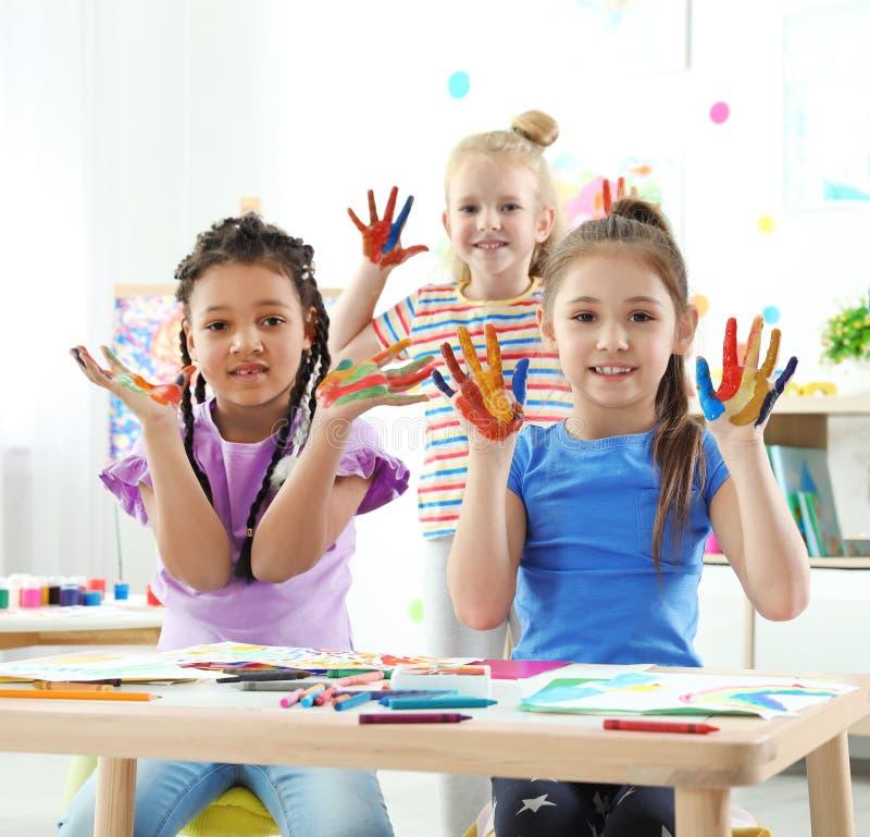 Nette kleine Kinder, die zuhause gemalte Hände an der Lektion zeigen stockbild