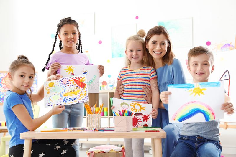 Nette kleine Kinder mit dem Lehrer, der ihre Malereien an der Lektion zeigt stockbild