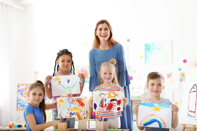 Nette kleine Kinder mit dem Lehrer, der ihre Malereien zeigt lizenzfreie stockfotografie