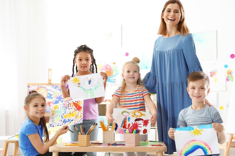 Nette kleine Kinder mit dem Lehrer, der ihre Malereien zeigt stockbilder