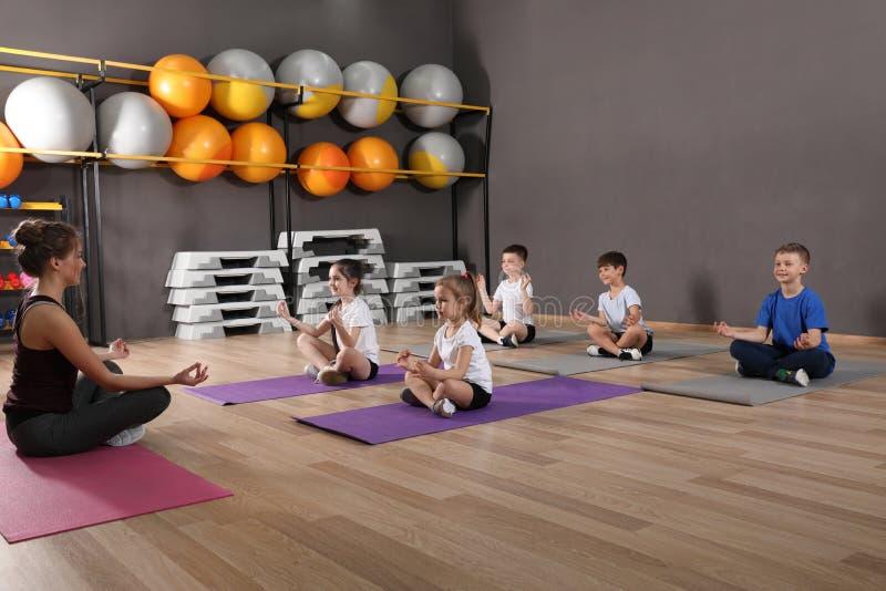 Nette kleine Kinder und Trainer, die körperliche Bewegung in der Schulturnhalle tut lizenzfreie stockfotografie