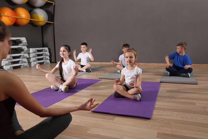 Nette kleine Kinder und Trainer, die körperliche Bewegung in der Schulturnhalle tut lizenzfreie stockfotos