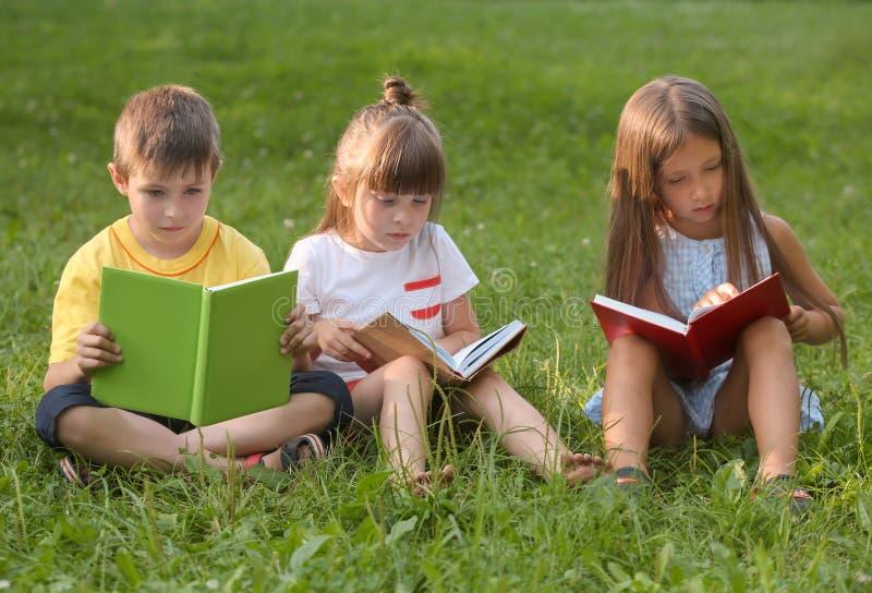 Nette kleine Kinderlesebücher im Park am Sommertag stockfoto