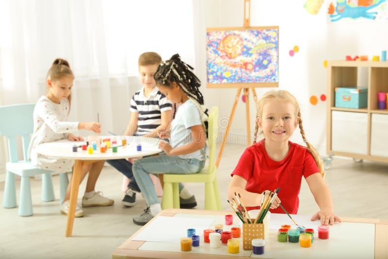 Nette kleine Kindermalerei an der Lektion lizenzfreie stockbilder