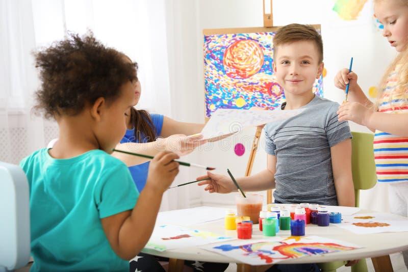 Nette kleine Kindermalerei an der Lektion stockbilder