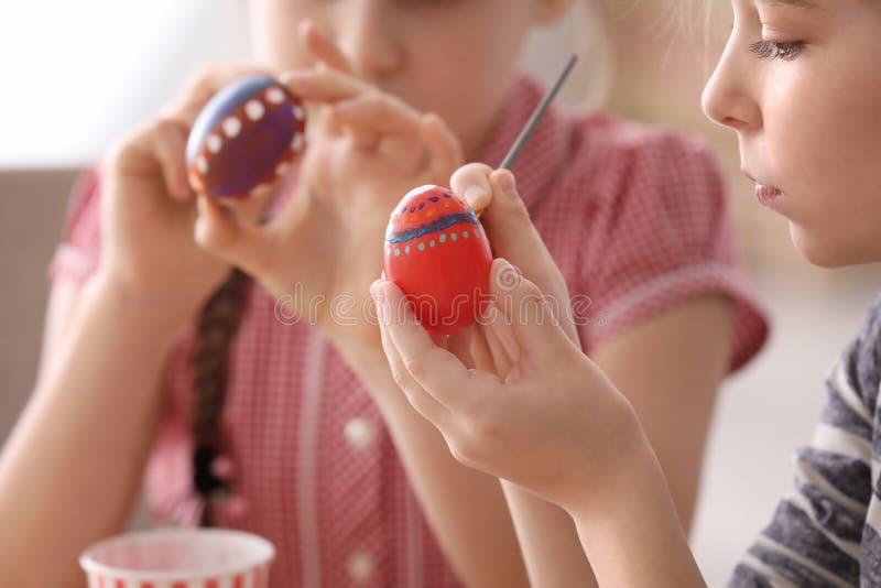 Nette kleine Mädchen, die Eier für Ostern, Nahaufnahme malen stockbild