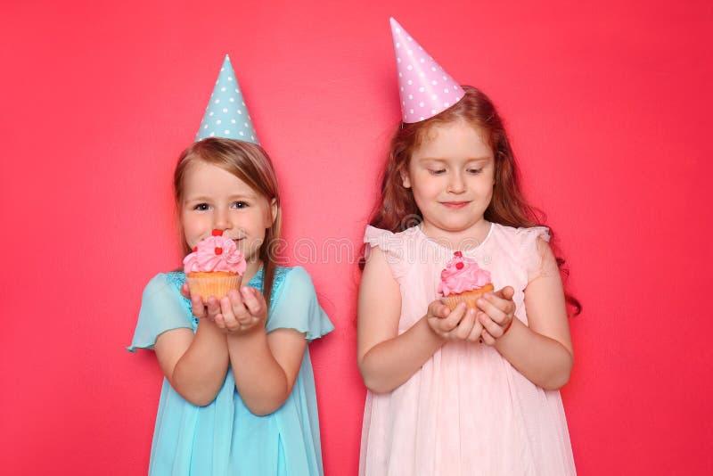 Nette kleine Mädchen mit Geburtstagskappen kleine Kuchen auf Farbhintergrund essend stockfotos