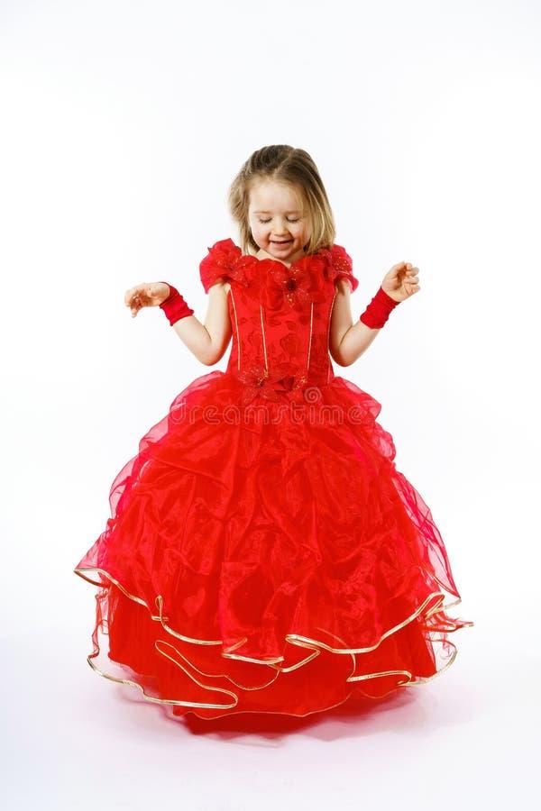 Nette kleine Prinzessin gekleidet im roten Tanzen lokalisiert auf weißem b stockbild