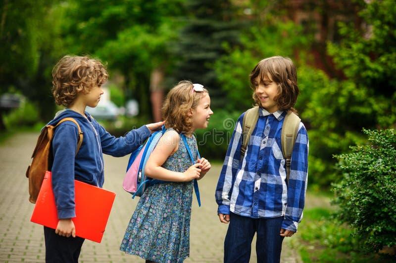 Nette kleine Schüler sprechen lebhaft auf dem Schulhof stockfotos