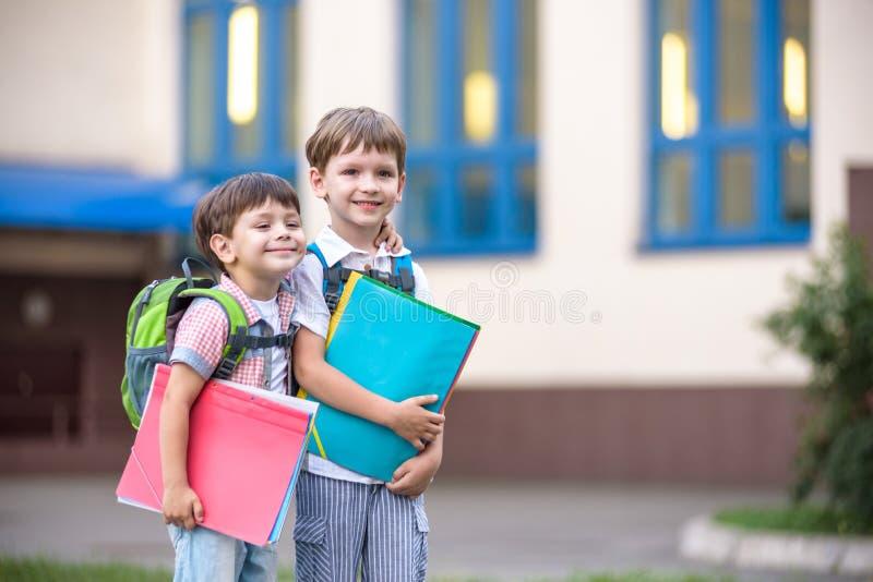 Nette kleine Schüler sprechen lebhaft auf dem Schulhof Chil lizenzfreie stockbilder