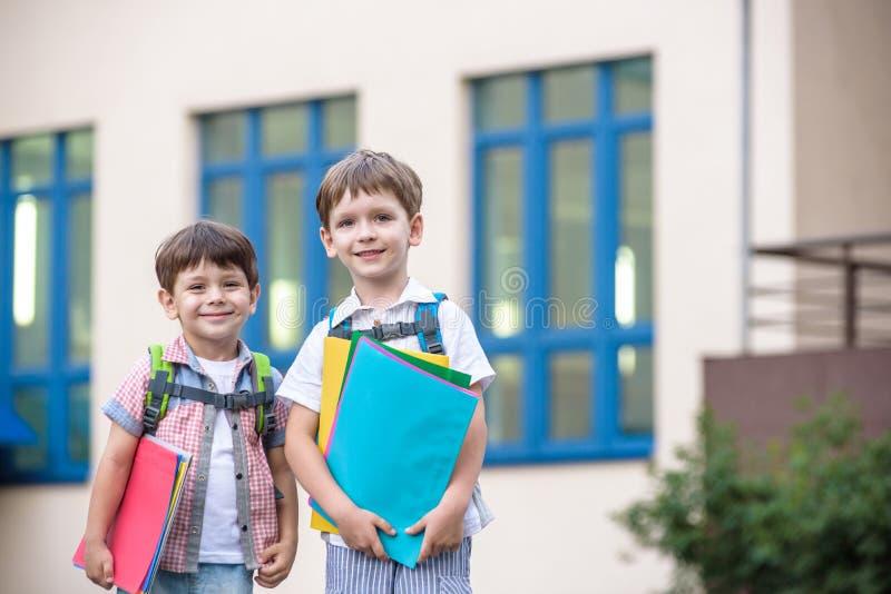 Nette kleine Schüler sprechen lebhaft auf dem Schulhof Chil lizenzfreie stockfotos