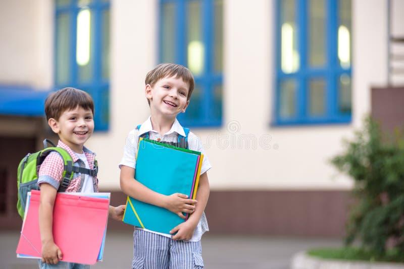 Nette kleine Schüler sprechen lebhaft auf dem Schulhof Chil stockfoto