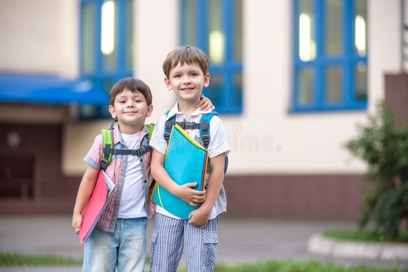 Nette kleine Schüler sprechen lebhaft auf dem Schulhof Chil stockbilder