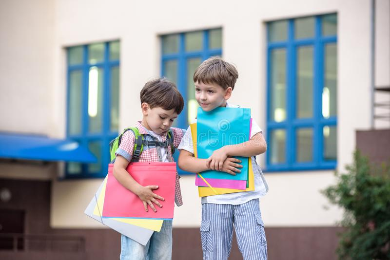 Nette kleine Schüler sprechen lebhaft auf dem Schulhof Kinder haben eine gute Laune Warmer Frühlingsmorgen stockbild