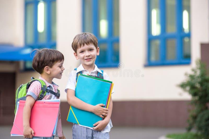 Nette kleine Schüler sprechen lebhaft auf dem Schulhof Kinder haben eine gute Laune Warmer Frühlingsmorgen stockfotografie