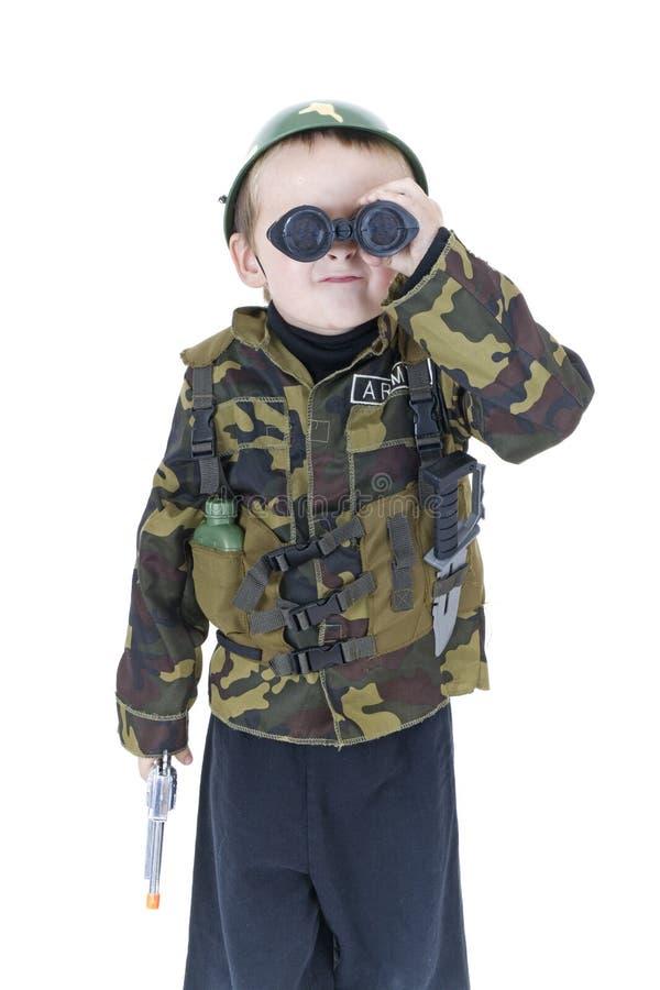 Nette kleiner Junge Grüße in der Armeeausstattung lizenzfreies stockbild