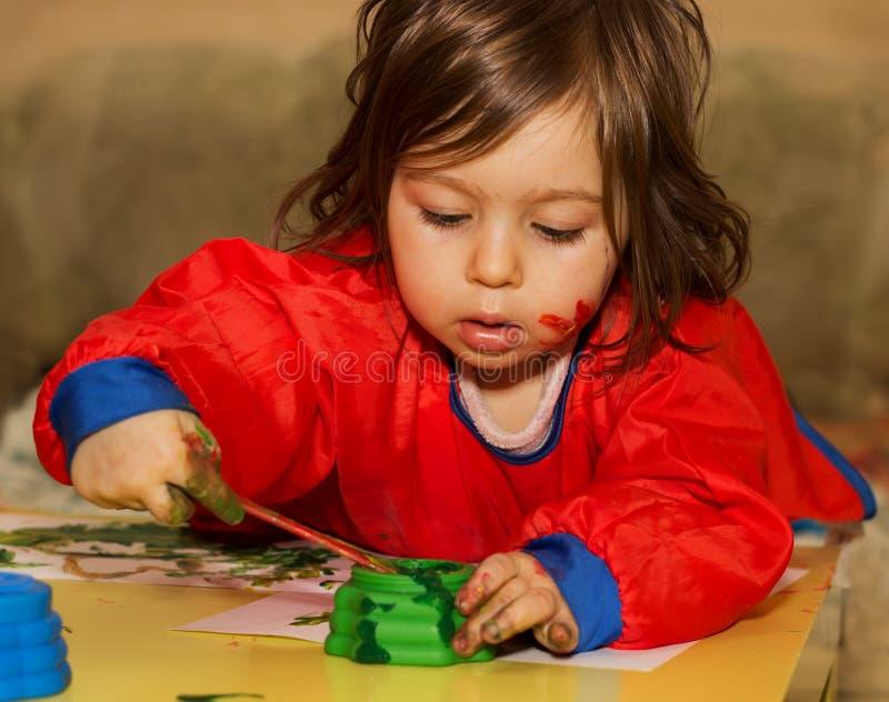 Nette kleines Kinderzeichnung und Studieren am Kindertagesstätte lizenzfreies stockfoto