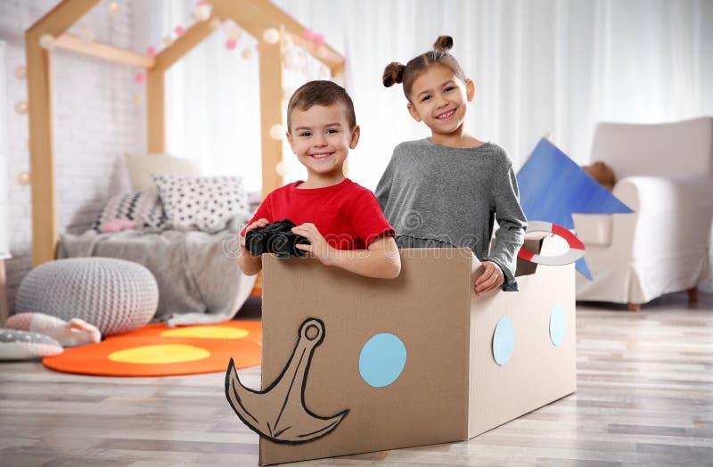 Nette Kleinkinder, die mit Ferngläsern und Pappboot spielen stockbild