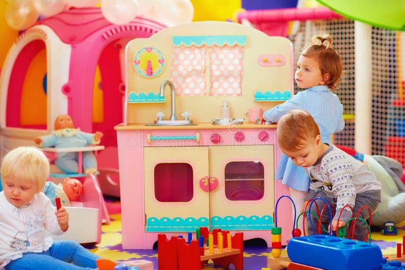 Nette Kleinkinder, die mit Spielwaren in der Kindertagesstättengruppe des Kindergartens spielen stockbilder