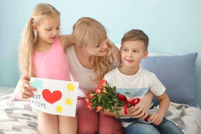 Nette Kleinkinder, die zu Hause ihre Mutter beglückwünschen lizenzfreie stockfotografie