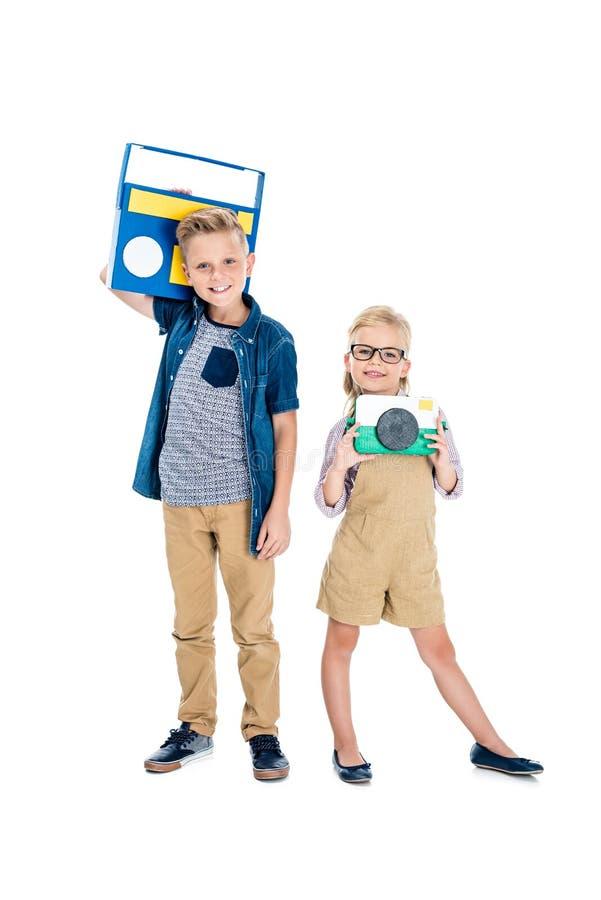 nette Kleinkinder mit Kamera und Tonbandgerät, das an der Kamera lächelt stockfoto