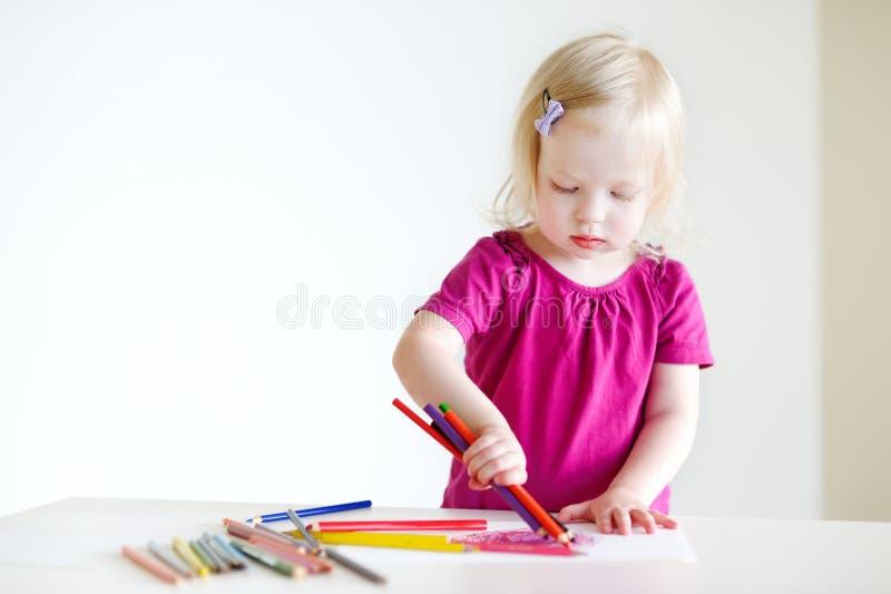 Nette Kleinkindmädchenzeichnung mit bunten Bleistiften stockfotos