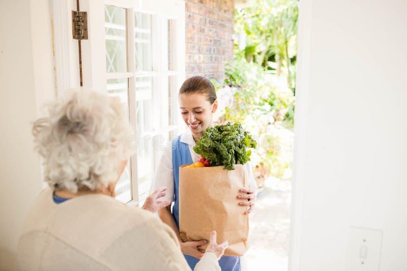 Nette Krankenschwester, die dem alten Patienten Gemüse holt lizenzfreie stockfotos