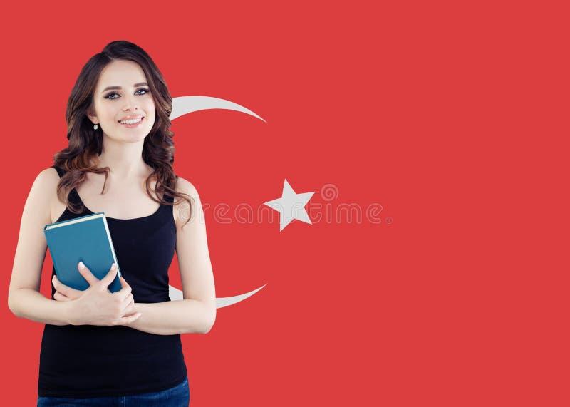 Nette lächelnde brunette Studentin mit Buch gegen türkischen Flaggenhintergrund Studie in der Türkei lizenzfreies stockbild